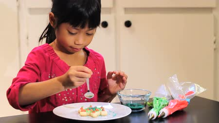 pişmiş : A cute 6 year old Asian girl adds sprinkles to her delicious looking Christmas cookie. Stok Video