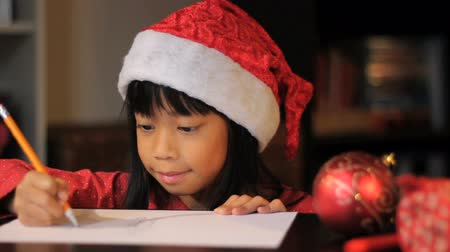 yazarak : A close up shot of a cute six year old Asian girl writes a letter to Santa Claus at Christmas time.