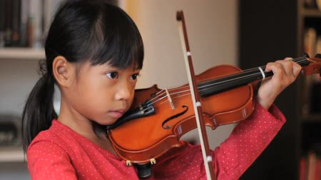 houslista : A pretty 6 year-old Asian girl diligently practices her violin in the living room.