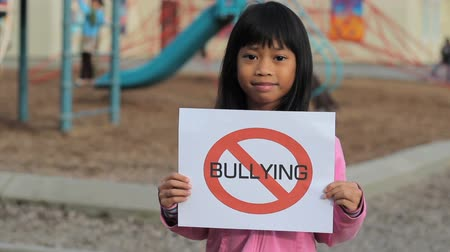 pletyka : A cute Asian girl holds up a large NO BULLYING sign on the school playground.