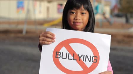сплетни : A cute Asian girl holds up a large NO BULLYING sign on the school playground.