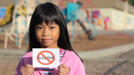 сплетни : A cute Asian girl holds up a small NO BULLYING sign on the school playground. Стоковые видеозаписи
