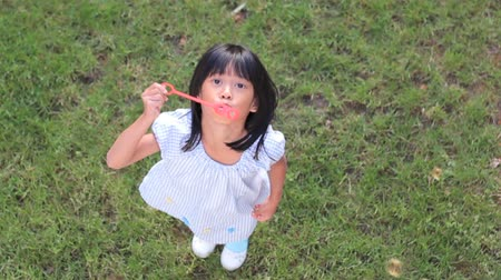 suçsuzluk : A cute little 6 year old Asian girl enjoys blowing bubbles into the air on a lovely summer day. Stok Video