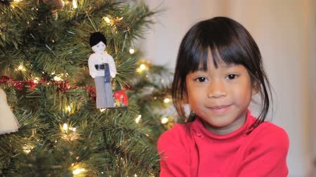 долл : A cute little 5 year old Thai girl hangs an Asian style Christmas ornament on her Christmas tree.
