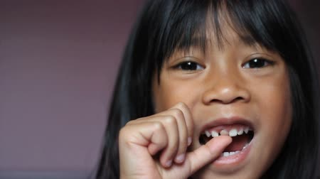 gevşek : A close up shot of a cute little 5 year old Asian girl wiggles her first loose front tooth.