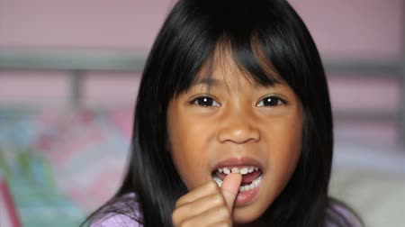 gevşek : A cute little 5 year old Asian girl wiggles her first loose front tooth.