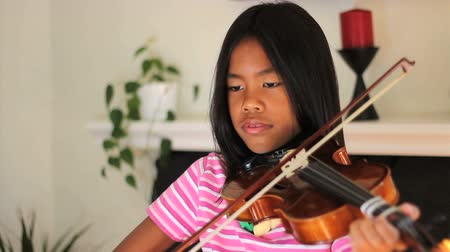 houslista : A pretty 9 year old Asian girl diligently practices her violin in the living room.