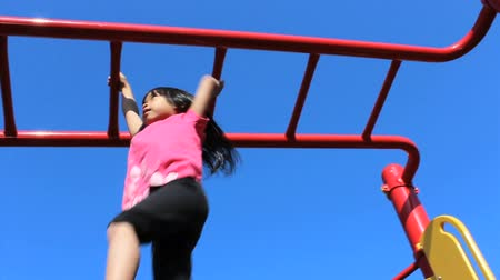 low lighting : A cute little Asian girl climbs successfully across the monkey bars at the school playground.