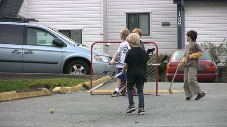 хоккей : A boy takes a wicked slap shot during a fun ball hockey game outside on the street.