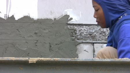 indústria : A pretty hard working Asian female construction worker uses her trowel to smooth cement on the side of a new office building in Hua Hin, Thailand.