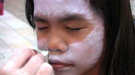ona : A beautiful Asian girl waits patiently while she gets her face paint applied.