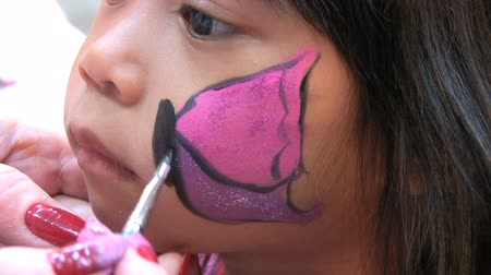 adil : A cute little Asian girl waits patiently while an artist paints a pretty pink butterfly on her face.