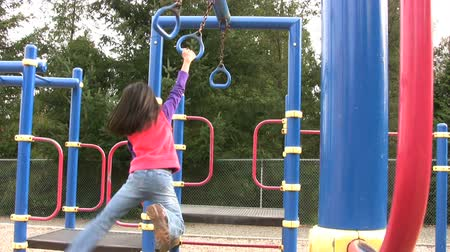 jimnastik : A young Thai girl enjoys hanging out on the school playground equipment doing the rings. Stok Video