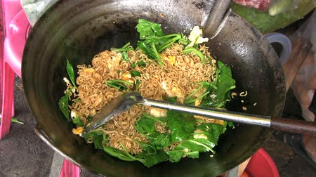 vegetable wok : A lady frying mama ramen noodles and vegetables at a local market in Bangkok, Thailand.