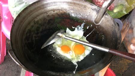 vegetable wok : A man fries eggs in a wok at the local market in Bangkok, Thailand.