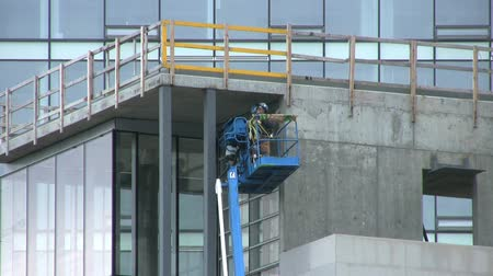 supervisor : A close up shot of a pair of building inspectors checking things over at a downtown construction work site.
