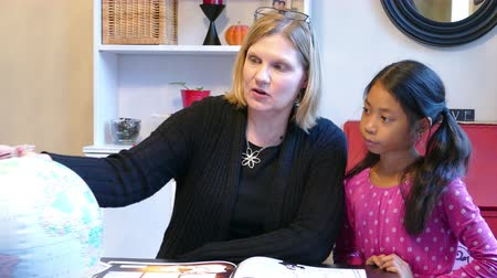 домохозяйка : A home school mom teaches a geography lesson to her cute 9 year old Asian daughter using a globe.
