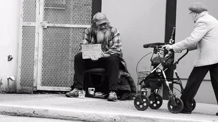 tek başına : VANCOUVER, BC, OCTOBER 2015: An old homeless man living on the streets says hello to a stranger on the streets of Vancouver, BC. Stok Video