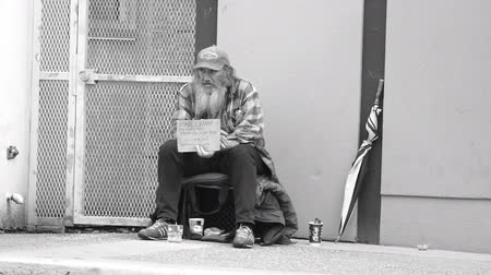 tramp : VANCOUVER, BC, OCTOBER 2015: An old homeless man living on the streets smokes a cigarette while waiting for donations on the streets of Vancouver, BC.