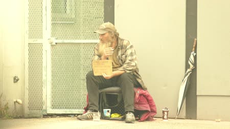 алкоголизм : VANCOUVER, BC, OCTOBER 2015: An old homeless man living on the streets smokes a cigarette while waiting for donations on the streets of Vancouver, BC.