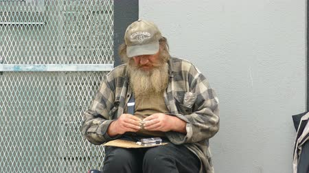 hijenik olmayan : VANCOUVER, BC, OCTOBER 2015: An old homeless man living on the streets rolls a cigarette while waiting for donations on the streets of Vancouver, BC.