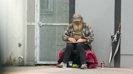 tek başına : VANCOUVER, BC, OCTOBER 2015: An old homeless man living on the streets prepares to roll a cigarette while waiting for donations on the streets of Vancouver, BC.
