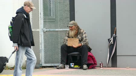 tek başına : VANCOUVER, BC, OCTOBER 2015: An old homeless man living on the streets chuckles at a man passing by on the streets of Vancouver, BC. Stok Video