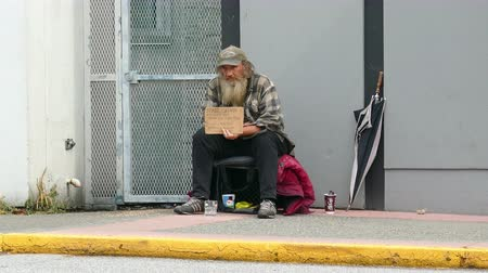 adomány : An old homeless man living on the streets waits for someone to come and give him a donation on the streets of Vancouver, BC.