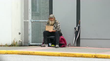 hijenik olmayan : VANCOUVER, BC, OCTOBER 2015: An old homeless man living on the streets waits for someone to come and give him a donation on the streets of Vancouver, BC.