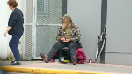 алкоголизм : An old homeless man living on the streets checks his coin jar after begging on the streets of Vancouver, BC.