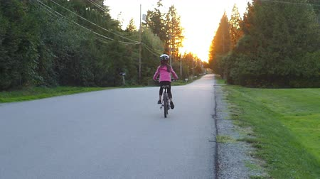 ciclismo : A cute 9 year old Asian girl enjoys a lovely fall bike ride while the sun sets on a country road. Vídeos