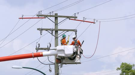 utilidade : A pair of hydro repair linemen work together to resolve various issues on a telephone pole in suburbia in the city of Vancouver.