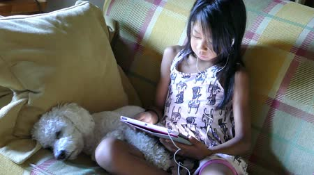 věrný : A cute little Asian girl uses her tablet alone in the living room with her faithful puppy at her side. Dostupné videozáznamy