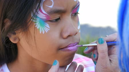 prenses : A cute Asian girl has fun getting her face painted at the local festival in the spring of 2015.