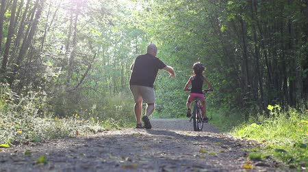 hrdý : An excited dad helps her young Asian daughter ride her new bike without training wheels for the first time on the pretty forest path.