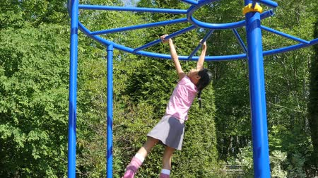 plac zabaw : A cute little 9 year old Asian girl enjoys the challenge of climbing on the monkey bars at the playground.