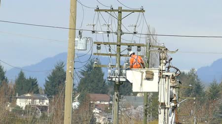 ludzik : A hydro repair lineman in an orange jumpsuit and hard hat repairs a problem on the line in the city of Vancouver.