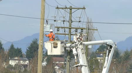 lineman : A hydro repair lineman in an orange jumpsuit and hard hat repairs a problem on the line in the city of Vancouver.