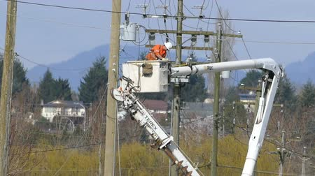utilidade : A hydro repair lineman in an orange jumpsuit and hard hat repairs a problem on the line in the city of Vancouver.