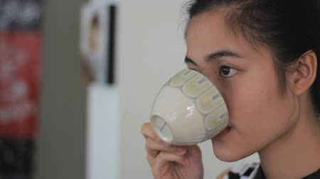 herbata : An attractive Asian young adult woman enjoys drinking coffee and spending time in a cafe in Bangkok, Thailand.