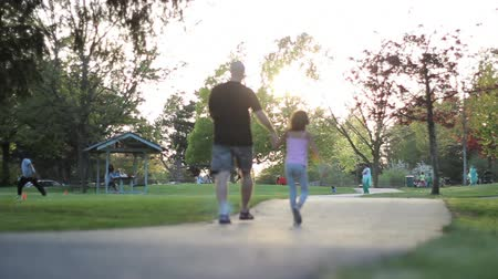 parky : A proud father and his eight year old daughter enjoy a walk in the park on a beautiful summer day.