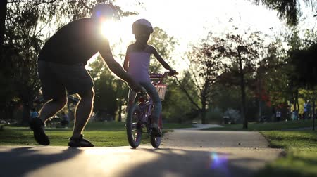 ailelerin : An excited dad helps her young Asian daughter ride her pink bike without training wheels for the first time.