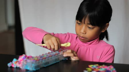 criar : A cute little 8 year old Asian girl has fun making colorful bracelets on her rainbow loom.