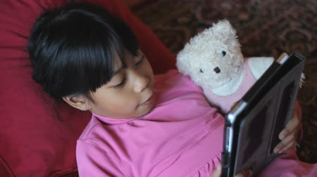touchpad : A cute little 8 year old Asian girl reads a story to her teddy bear using her new digital tablet.