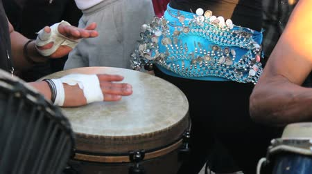 enstrüman : A close up shot of a djembe drummer lays down a funky beat while a female belly dancer dances in the Drum Circle at Venice Beach, California.