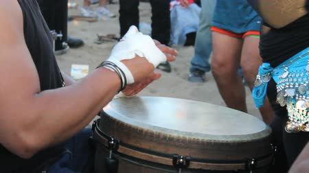 enstrüman : A djembe drummer lays down a funky beat while a female belly dancer dances in the Drum Circle at Venice Beach, California. Stok Video