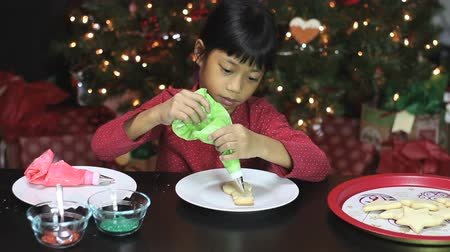 tradição : A cute little seven year old Asian girl enjoys making beautiful Christmas cookies in time for the holiday season.