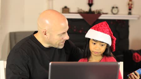 świety mikołaj : A father and daughter enjoy spending time together and doing some online Christmas shopping using their laptop and credit card.