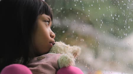 tek başına : A depressed little seven year old Asian girl sits by a rainy window with her Teddy Bear.
