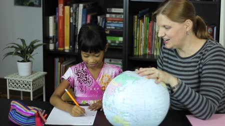ödev : A homeschool mom teaches a geography lesson to her cute 7 year old Asian daughter using a globe.
